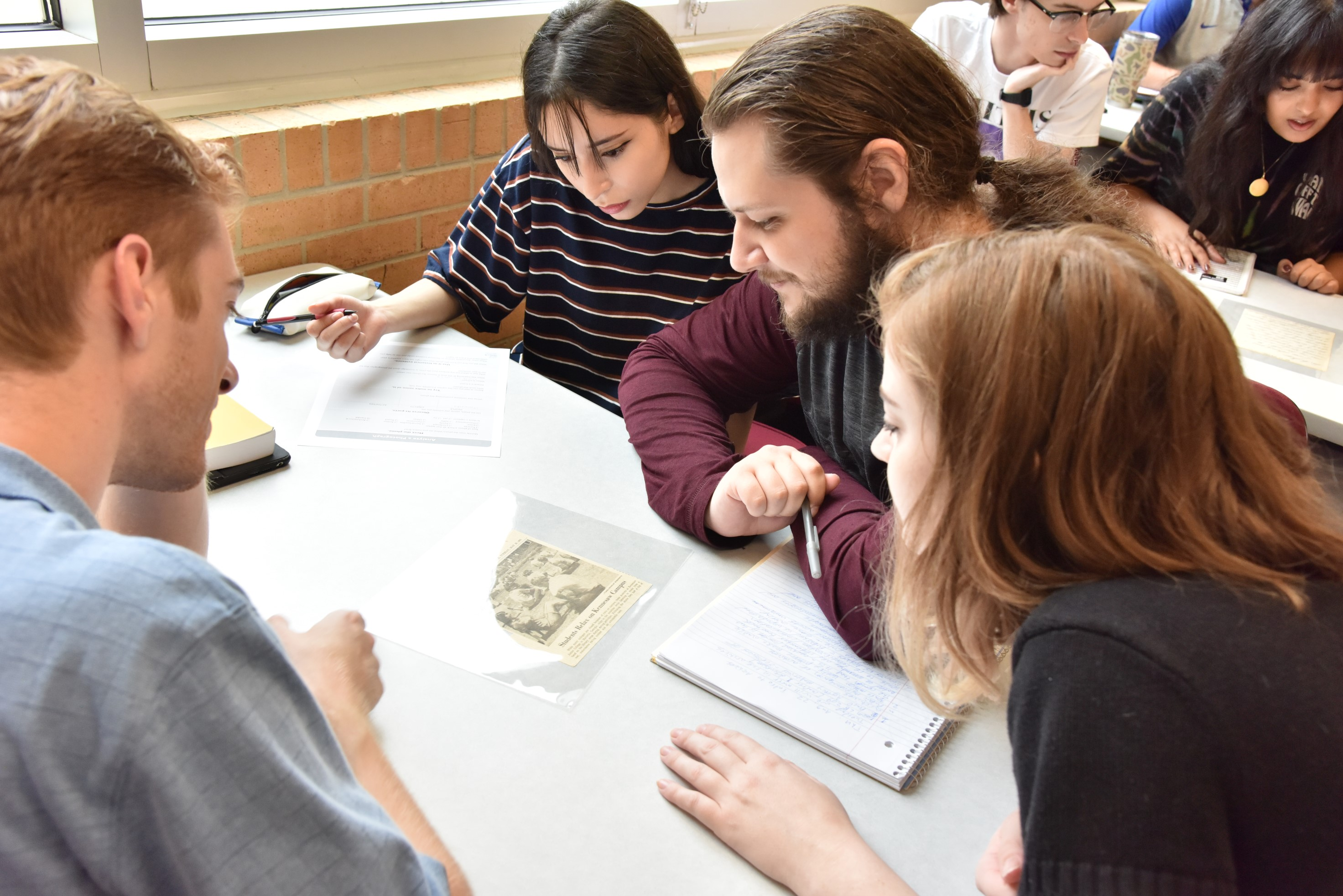 Students examine a clipping from the Stella Merritt Collection.